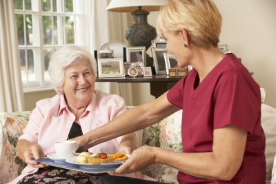 a photo of a caregiver serving a senior woman her meal